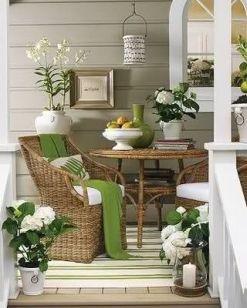Zgaszona, pastelowa zieleń o odcieniu khaki na ścianach, uwypukla i harmonizuje ciepłą naturalną zieleń dodatków i brąz wikliny